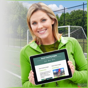 Lady soccer coach holding tablet with the newsletter on a soccer field.