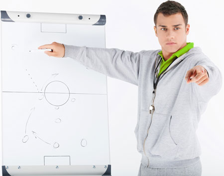 Soccer coach going over play on writing board