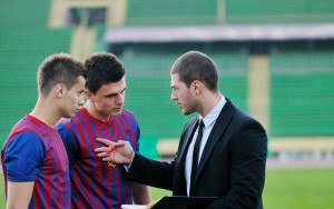 Professional soccer coach talking to two players