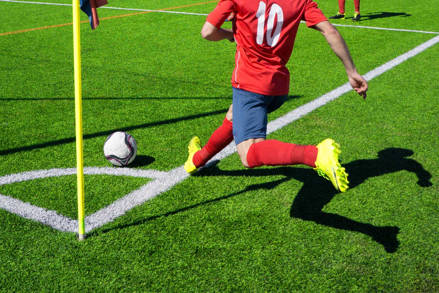 Red uniformed player kicking a corner penalty kick.